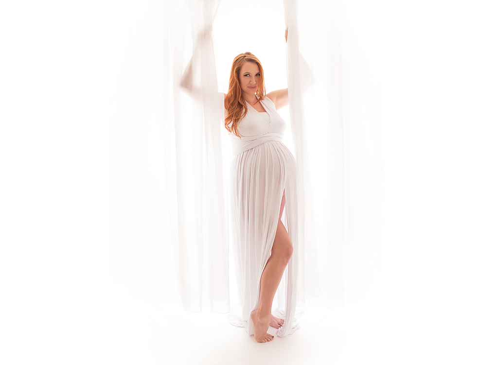 Beautiful mother to be in all white behind sheer curtain | Pleasantly Captured Photography | Maternity Photographer Jacksonville, NC
