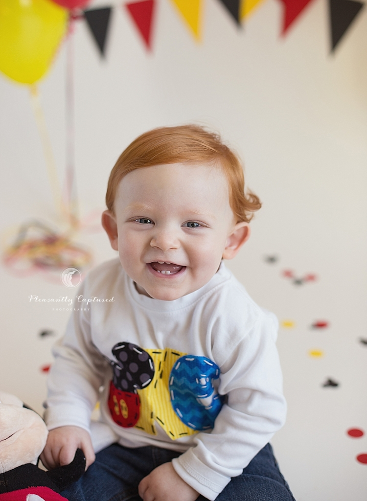 Little boy smiles while holding Mickey Mouse plush doll | Pleasantly Captured Photography | Baby Photographer Jacksonville NC