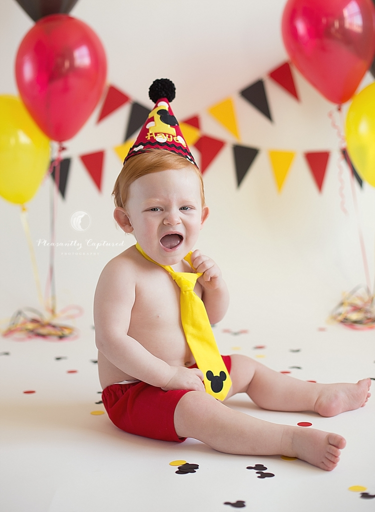 Little boy not happy with wearing his Mickey Mouse cake smash outfit | Pleasantly Captured Photography Cake Smash Photographer Jacksonville