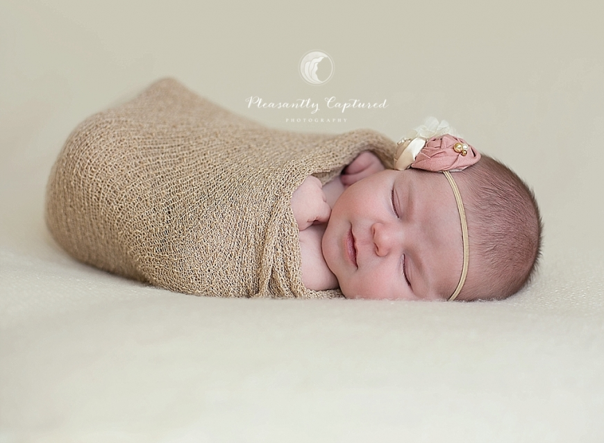 Newborn girl giving a little smirk while sleeping pleasantly captured photography newborn photography jacksonville nc