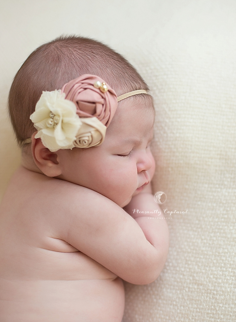 P i n newborn girl laying on side with bow pleasantly captured photography jacksonville nc premiere newborn photography