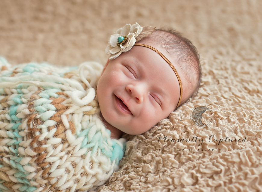 Al newborn girl smiling pleasantly captured photography nc newborn photographer