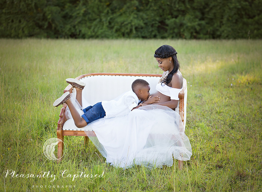 Mother To Be Lays In Vintage Settle As Her Son Kisses Pregnant Belly