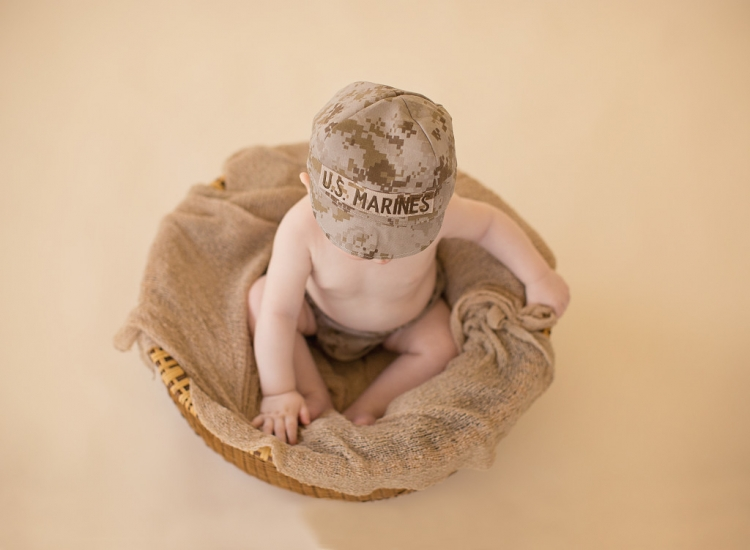 Baby boy wearing marines cover plays with feet in basket - Baby photography studio Jacksonville, NC