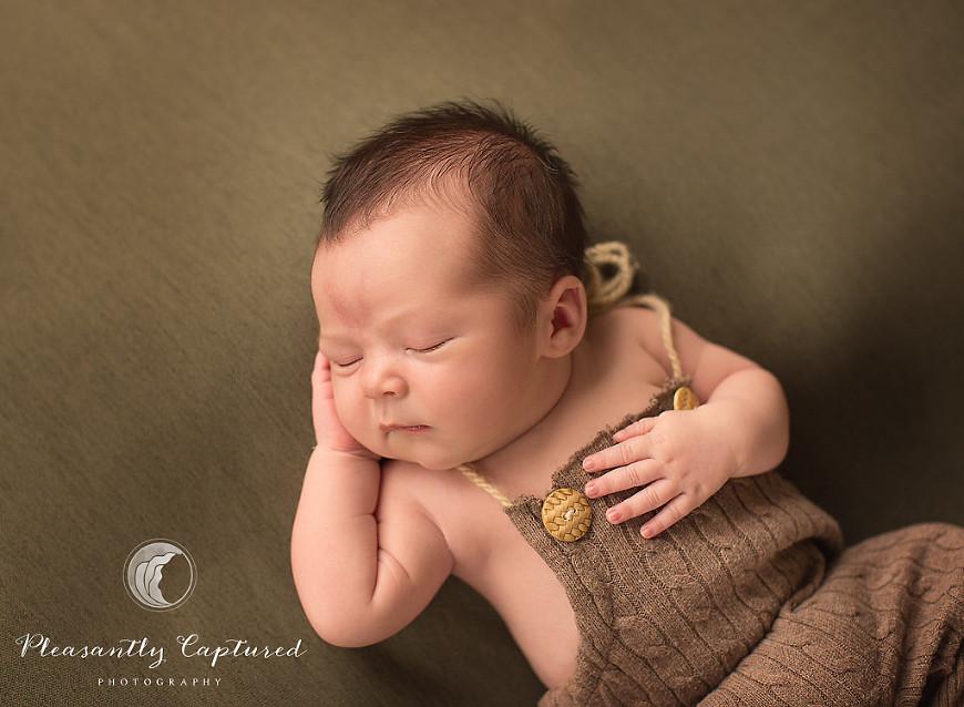 Newborn boy sleeps peacefully in cute newborn romper - Pleasantly Captured Photography - Baby photographer Jacksonville NC