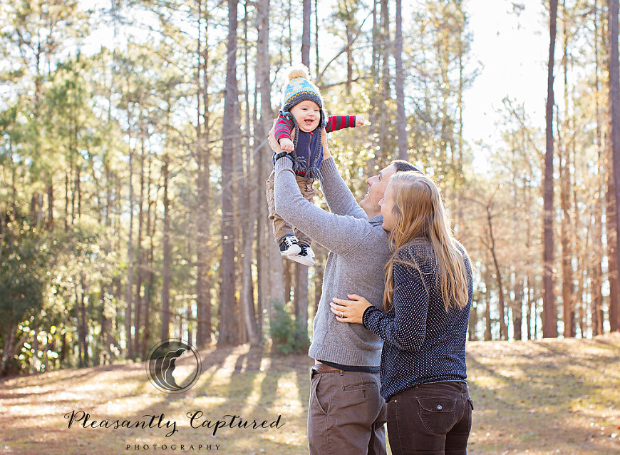 Baby boy smiles at parents while dad lifts him up into the air - Pleasantly Captured Photography - Camp Lejeune NC Photographer