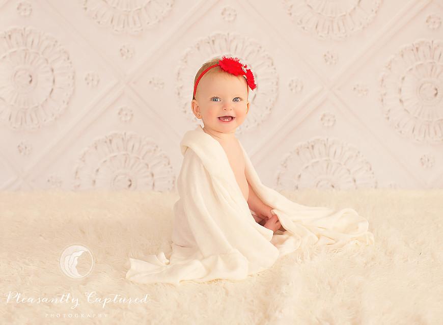 Baby girl wears red headband draped in cream blanket - Pleasantly Captured Photography - Swansboro NC Baby Photographer