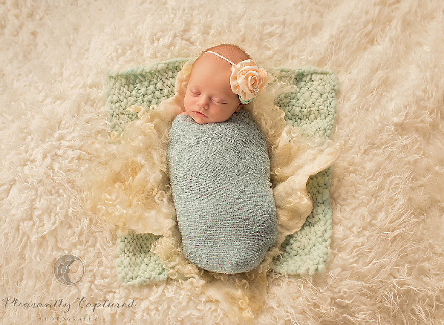 Newborn girl sleeps with pretty bow on a textured blanket pleasantly captured photography newborn