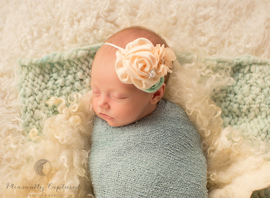 Newborn girl sleeps peacefully swaddles on top of furry blankets - Pleasantly Captured Photography - Newborn-Baby Photographer Jacksonville NC