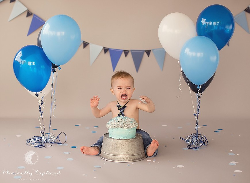 Baby boy gets upset while eating his cake - Pleasantly Captured Photography - Baby Photographer Jacksonville NC