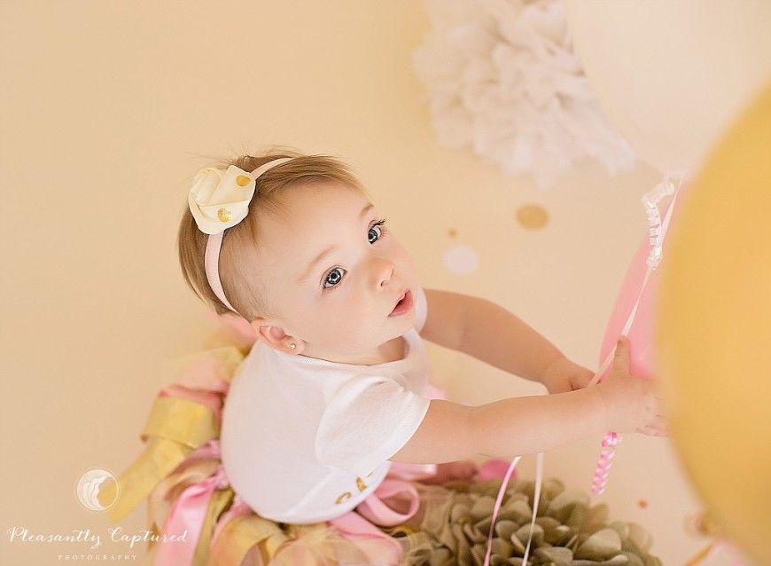 One year old girl plays with balloons during her birthday session - Pleasantly Captured Photography - Jacksonville Baby Photographer
