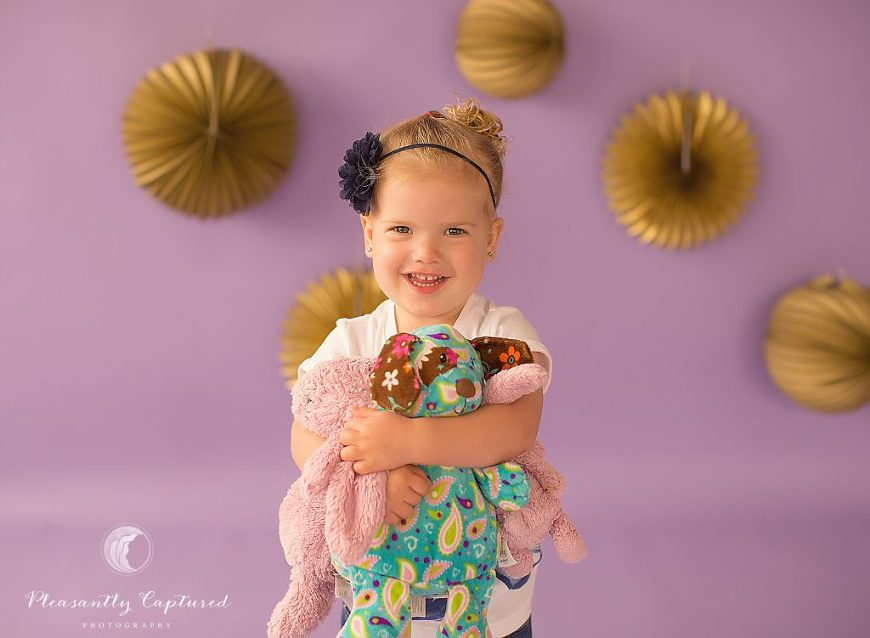 Little girl smiles as she snuggles her stuffed animals - Pleasantly Captured Photography - Child Photographer Jacksonville NC