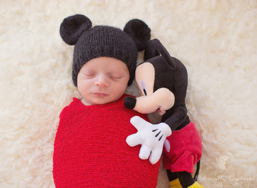 Newborn boy dressed as Mickey Mouse with his Mickey Mouse stuffed animal hugging him - Pleasantly Captured Photography - Newborn-baby photographer jacksonville nc