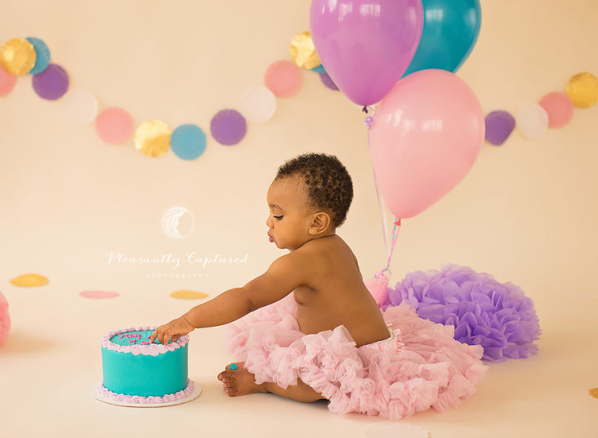 Baby girl reaching to touch birthday cake - Pleasantly Captured Photography - First Birthday Photography Jacksonville NC