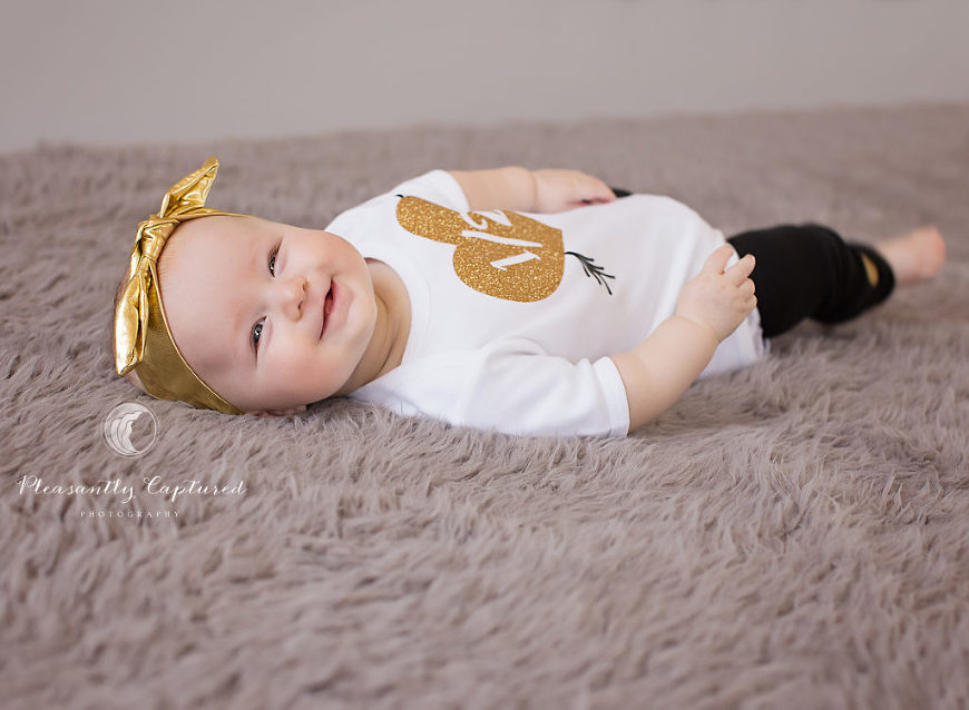 Baby girl smiling while laying on back - Pleasantly Captured Photography - Baby Photography Jacksonville NC